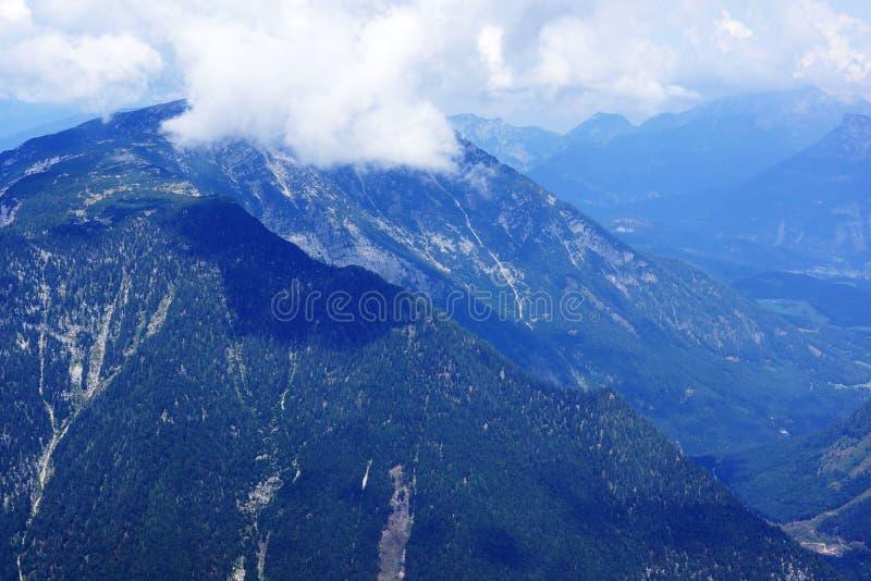 Le montagne maestose blu e le riflessioni delle nuvole enormi sui picchi fotografie stock libere da diritti