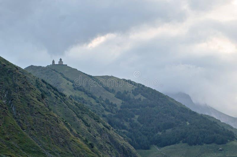 Le montagne nuvolose di Georgia Europe Kazbegi della chiesa di trinità di Gergeti abbelliscono Caucaso fotografia stock libera da diritti
