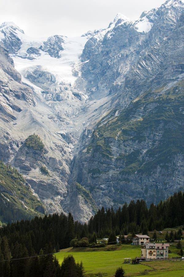 Le montagne rocciose severe hanno coperto di neve e ghiacciano una valle verde con gli abeti e le case fra loro fotografia stock libera da diritti
