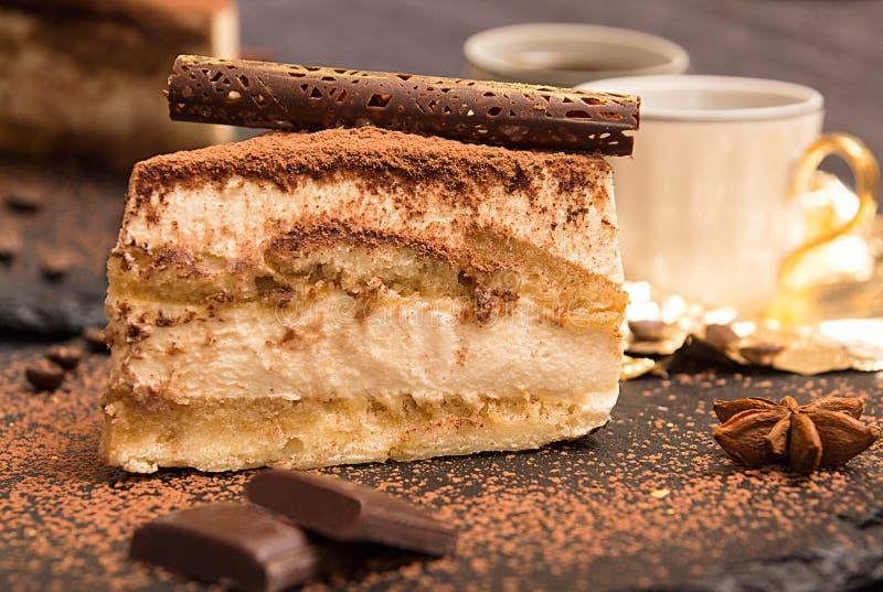 Le morceau de gâteau de tiramisu sur l'ardoise noire garnissent avec la menthe et le chocolat photo stock
