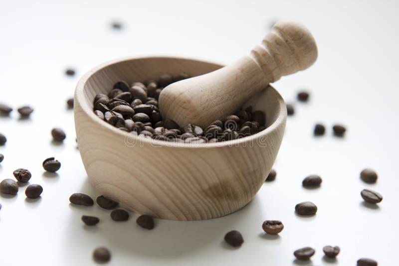 Le mortier en bois a rempli de graines de café entières photos libres de droits