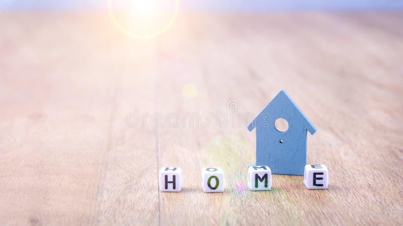 Le mot À LA MAISON des lettres de cube devant le bleu a coloré le symbole de maison sur la surface en bois images stock