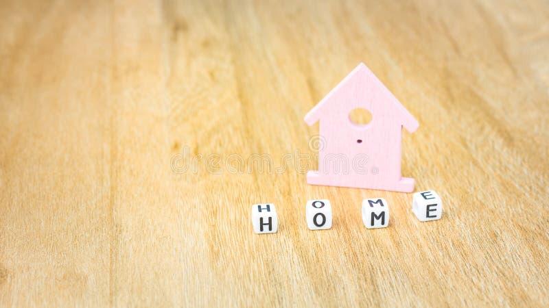 Le mot À LA MAISON des lettres de cube devant le lilas a coloré le symbole de maison sur la surface en bois images stock