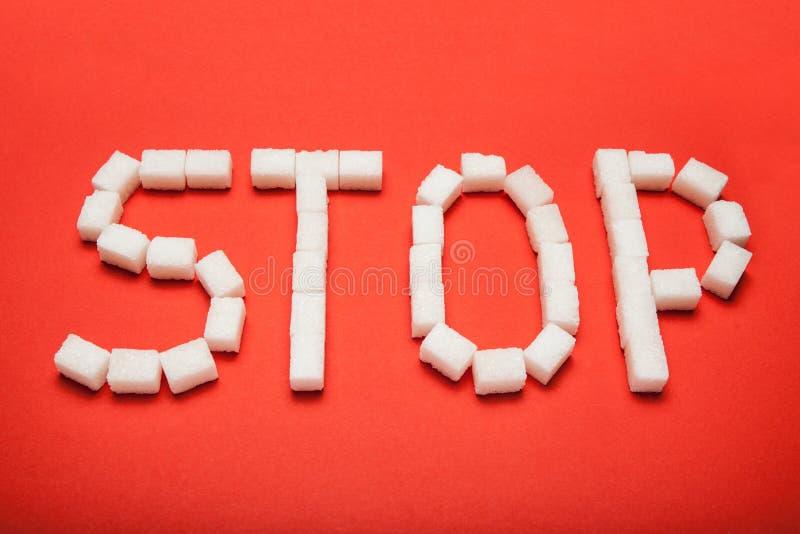 """Le mot """"arrêt """"des cubes de sucre sur un fond rouge images libres de droits"""