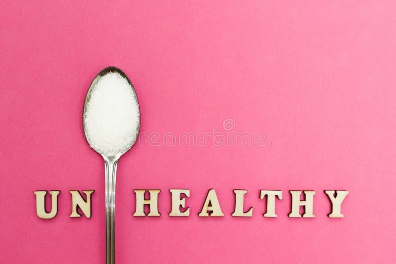 """Le mot le """"ONU sain """", une cuillère avec du sucre sur un fond rose, concept photographie stock"""