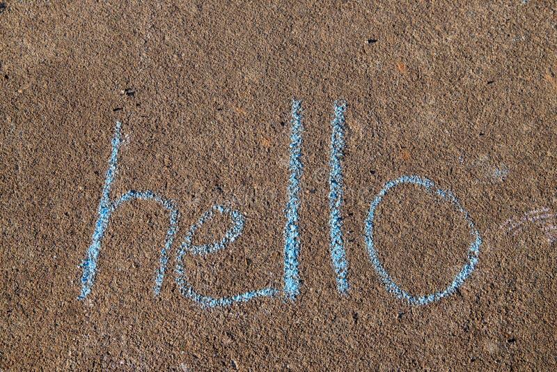 Le mot bonjour écrit avec la craie de trottoir sur le fond gris de revêtement bétonné photos libres de droits
