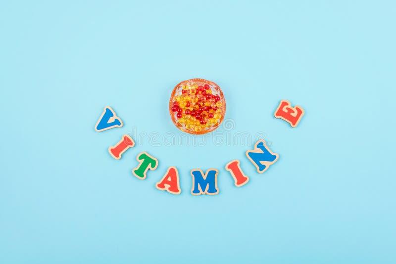 Le mot de la vitamine E a coloré les lettres en bois sur le fond bleu photo libre de droits