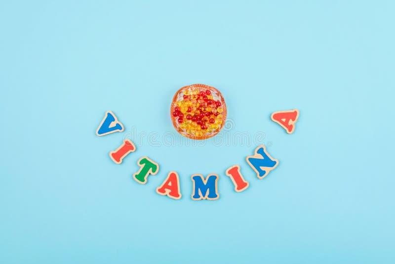 Le mot de vitamine A a coloré les lettres en bois sur le fond bleu image stock