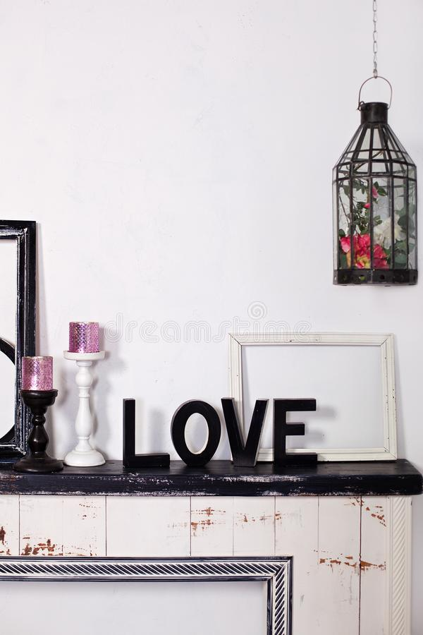 Le mot en bois est amour Sur la chemin?e sont deux chandeliers avec des bougies et l'amour en bois de mot Inscription d'amour dan image libre de droits