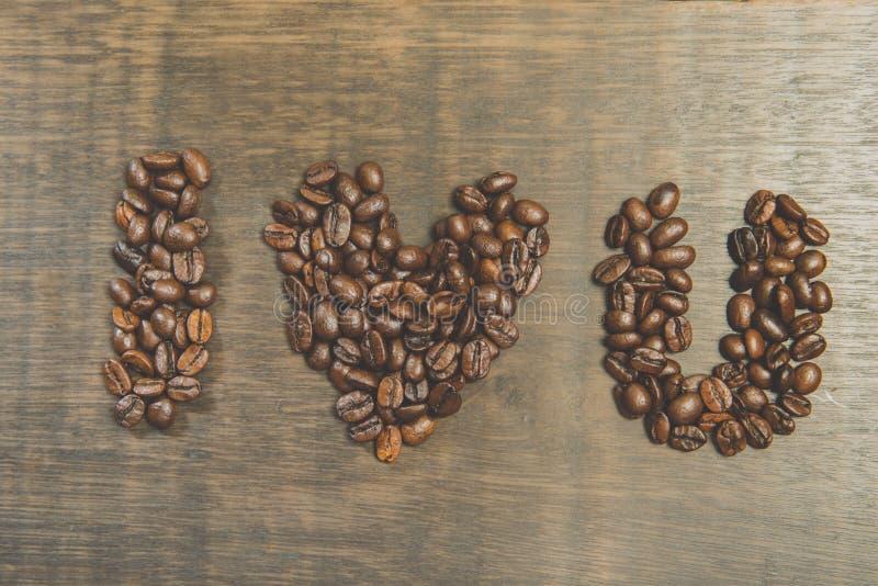 Le mot je t'aime fait à partir des grains de café sur la table en bois Stil photo stock