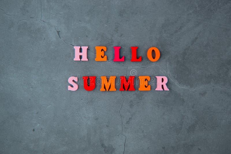 Le mot multicolore d'été de bonjour est fait de lettres en bois sur un fond plâtré gris de mur photographie stock