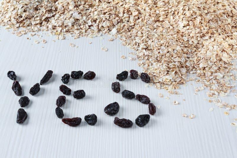 Le mot oui des raisins secs et des flocons d'avoine entiers sur la table blanche image stock