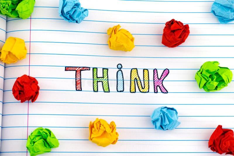 Le mot pensent sur la feuille de carnet avec quelques boules de papier chiffonnées colorées autour de lui photo libre de droits