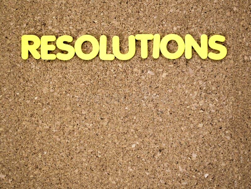 Le mot RÉSOLUTIONS définies dans les lettres jaunes sur un panneau de liège photo libre de droits