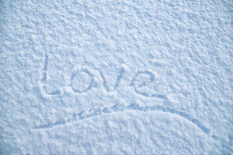 """Le mot souligné manuscrit """"amour """"est écrit sur la neige pelucheuse, une soirée givrée d'hiver Jour du `s de Valentine image libre de droits"""