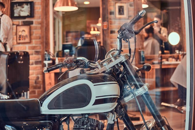 Le motobike de cru est garé à l'intérieur au raseur-coiffeur à la mode photo stock