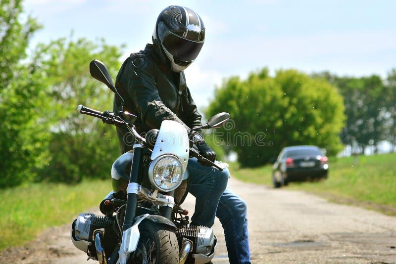 Le motocycliste dans le casque et la veste en cuir s'assied sur sa moto photo libre de droits
