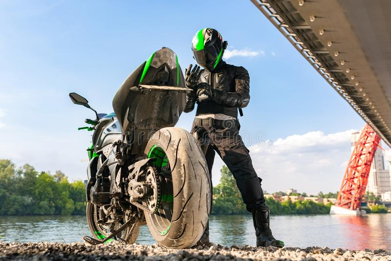 Le motocycliste dans un casque et dans une tenue de protection se tient sous le pont image stock