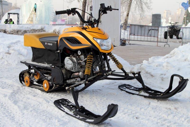 Le motoneige jaune se tient près de la ville de glace sur la rue du photographie stock libre de droits