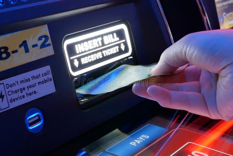 Le mouvement de la femme insère l'argent sur la machine à sous à l'intérieur du casino images libres de droits