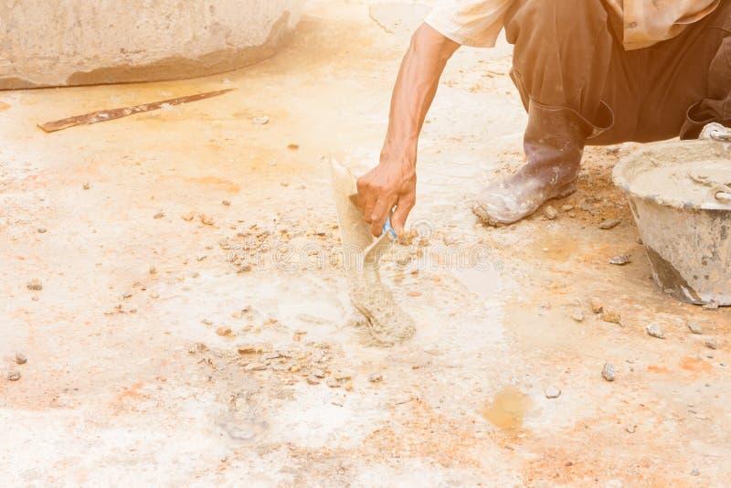 Le mouvement de travailleurs de la construction plâtraient le plancher de réparation dans la construction de lieu de travail une  photographie stock