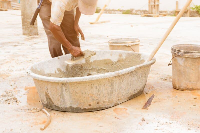 Le mouvement de travailleurs de la construction plâtraient le plancher de réparation dans la construction de lieu de travail une  photos libres de droits
