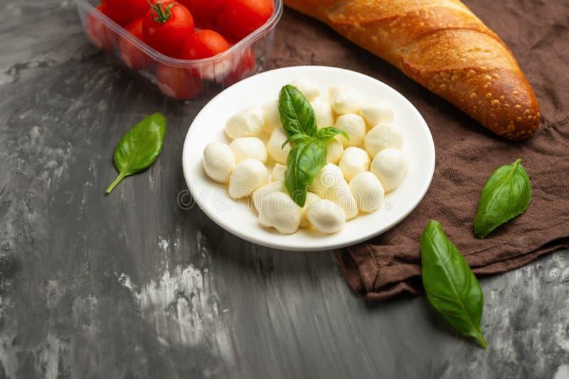 Le mozzarella avec le basilic laisse - les ingrédients frais pour la bruschette, avec les tomates-cerises et la baguette français photos stock