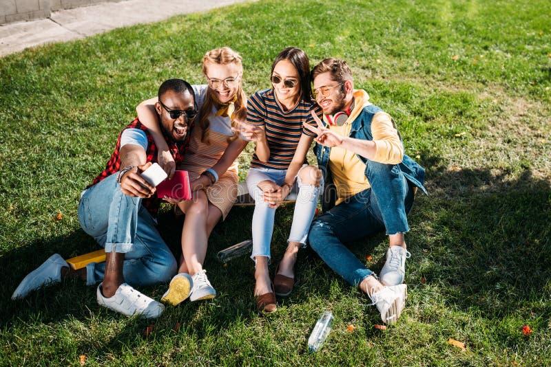 le multietniska vänner som tar selfie på smartphonen, medan vila på gräsplan arkivfoto
