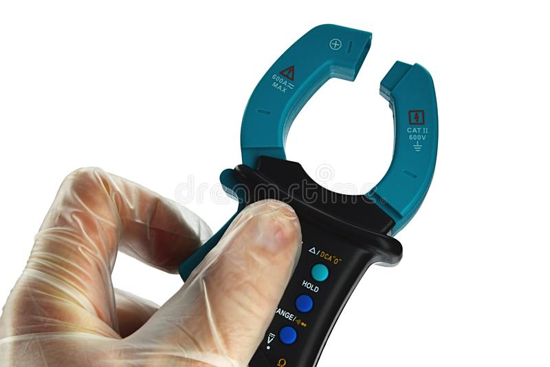 Le multimètre électrique de bride moderne s'est tenu dans la main gauche dans le gant transparent de latex, fond blanc image libre de droits