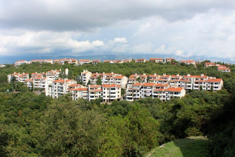 Le multiple a attaché les immeubles blancs du côté de la colline entouré avec les maisons denses de végétation forestière et de f image stock