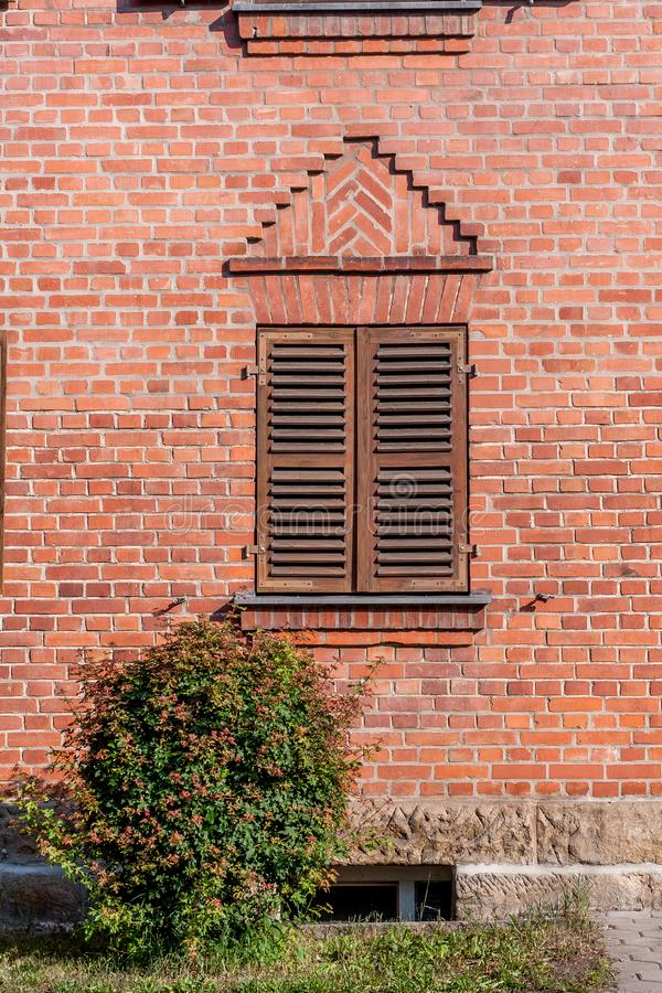 Le mur de briques avec la fenêtre et wodden des volets image libre de droits