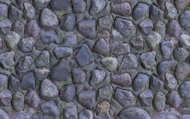 Le mur empilé par pierres foncées gris-clair de Panne de la vieille fontaine sèche a survécu au fond texturisé de plan rapproché images stock