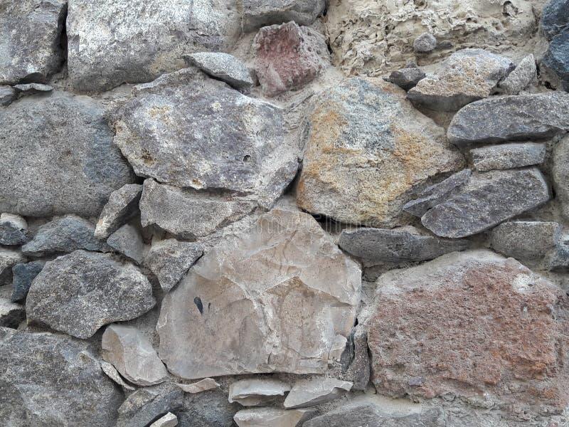 Le mur en pierre rose, gris, beige a donné au fond une consistance rugueuse des roches sèches primitives de pile étendues dans le photos libres de droits