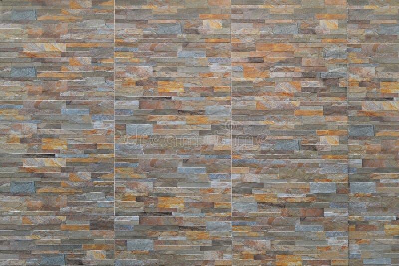 Le mur a garni des carreaux de céramique, imitant une maçonnerie faite en pierre de différents types et couleurs photographie stock