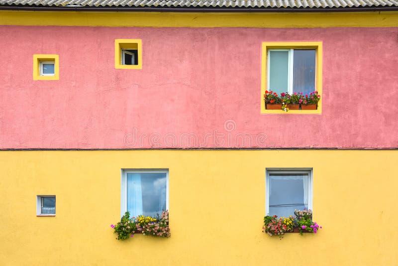 Le mur multicolore lumineux de maison, fleurs sont sur les fenêtres photos stock