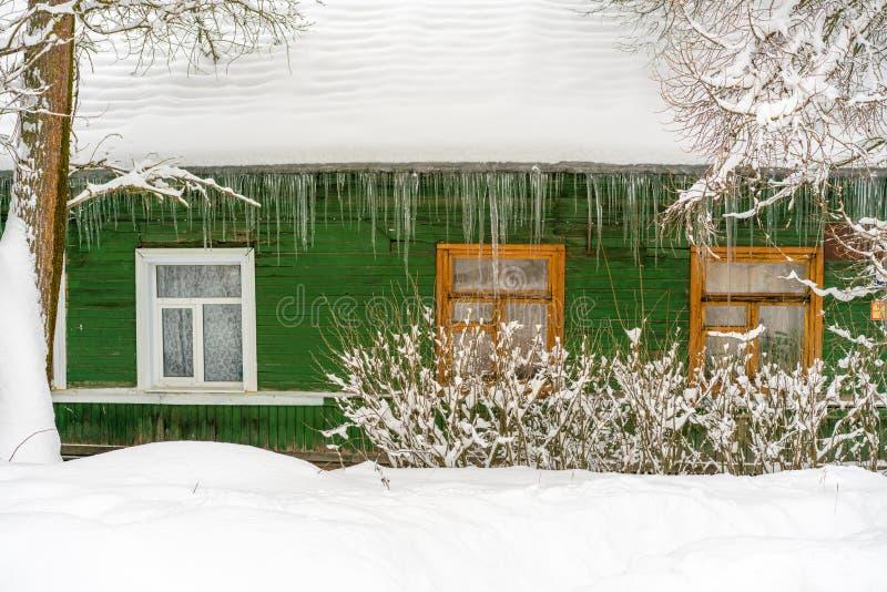 Le mur vert de la maison en bois de vieux-mode russe avec les fenêtres en bois, le toit couvert par la neige et les glaçons énorm photographie stock libre de droits