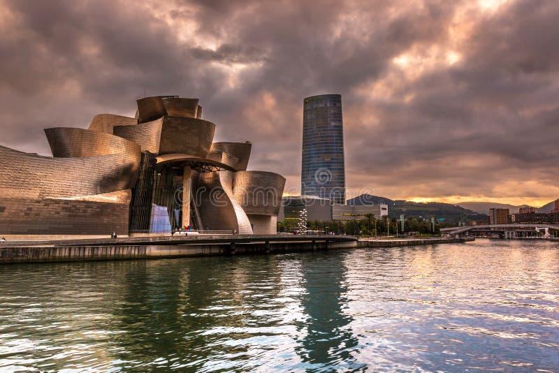 Le musée de Guggenheim Bilbao et tour d'Iberdrola au coucher du soleil dramatique images stock