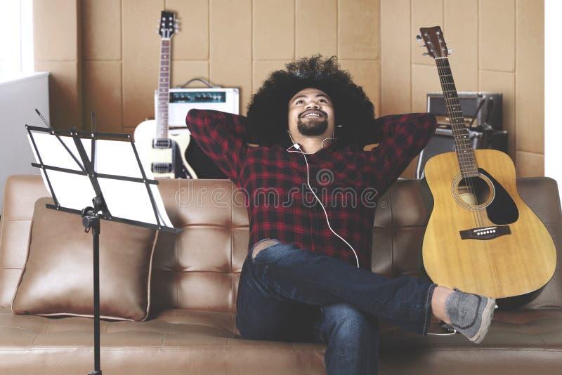 Le musicien écoute la musique trouvant l'inspiration pour écrire une chanson photographie stock libre de droits