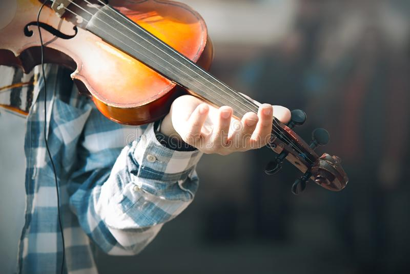 Le musicien de rue de mendiant joue un vieux violon usé de sortie image stock