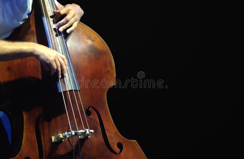 Le musicien jouant la double basse photo stock