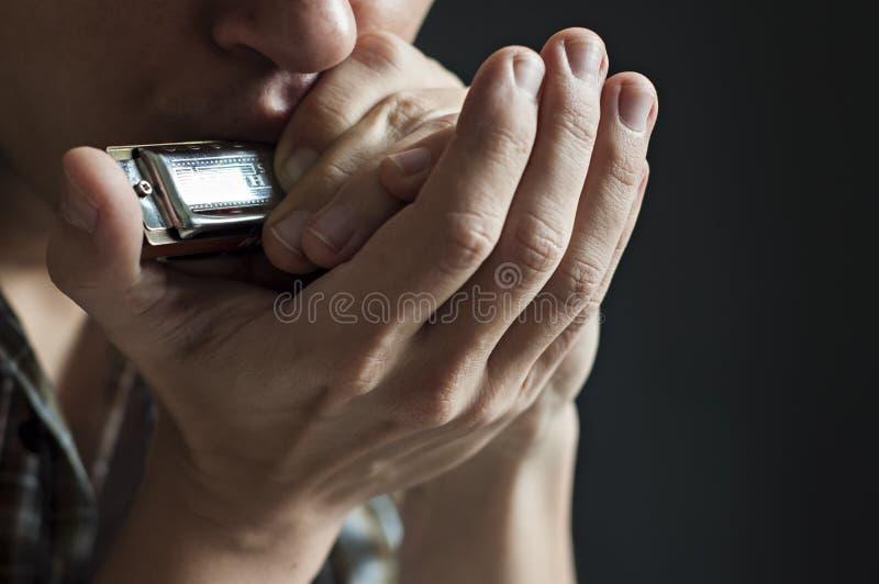Le musicien joue l'harmonica image libre de droits