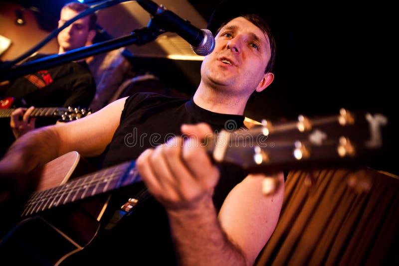 Le musicien joue une guitare image stock