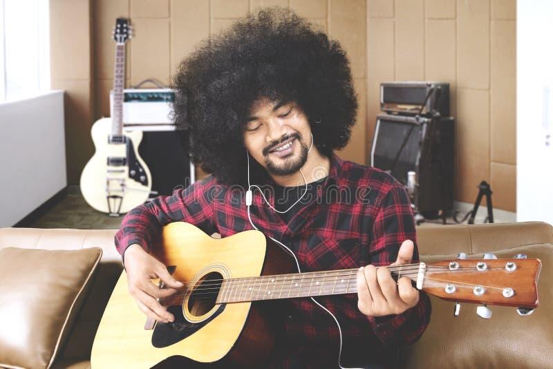 Le musicien masculin joue la guitare dans le studio d'enregistrement photo libre de droits