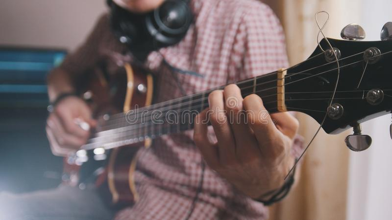 Le musicien masculin joue la guitare, mains se ferment  photo stock