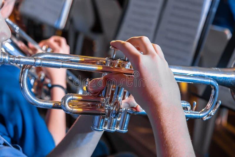 Le musicien masculin remet tenir et jouer la trompette dans un concert de bande images stock
