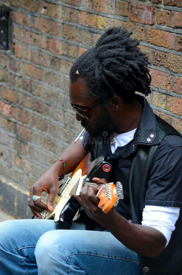 Le musicien noir de rue s'assied contre la guitare Londres Angleterre de jeux de mur image libre de droits