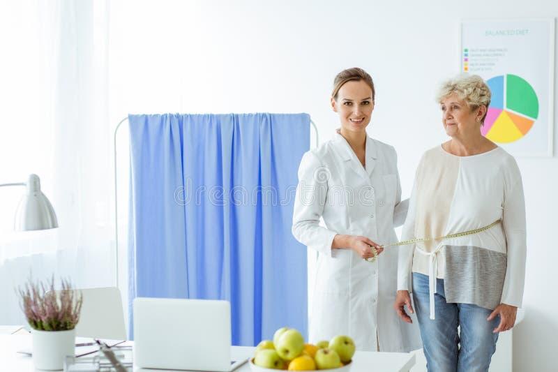 Le näringsfysiologen som mäter patienten royaltyfria bilder
