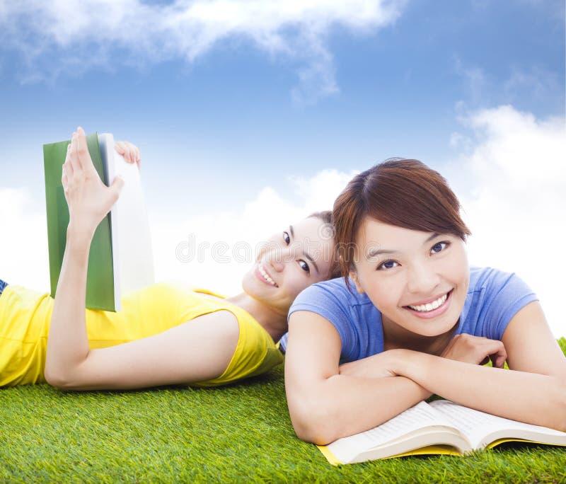 Le nätta studenter som ligger på grässlätten med böcker arkivfoton
