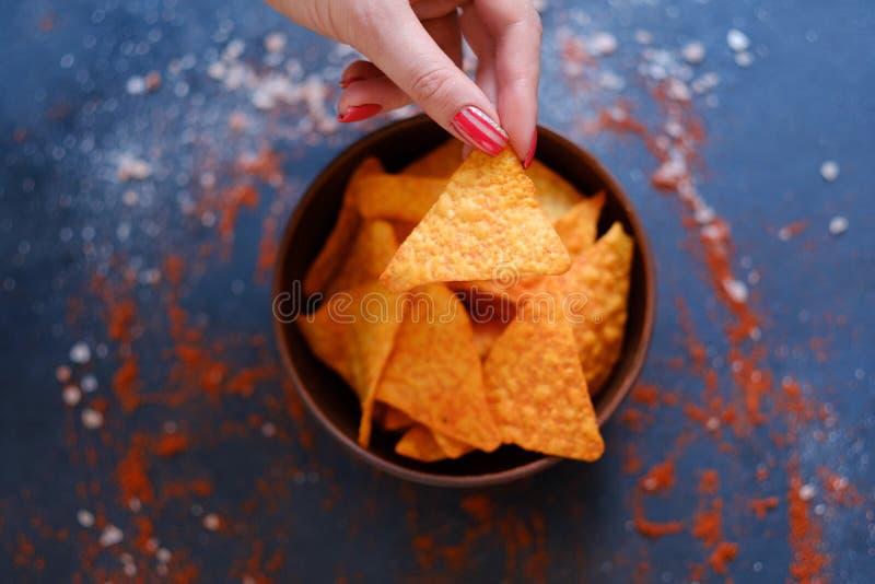 Le nacho de tortilla ébrèche la main de recette tenant des chips images stock