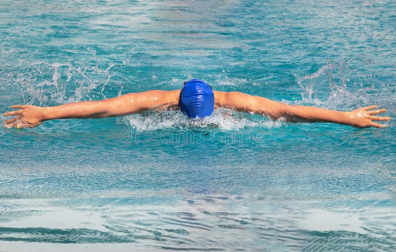 Le nageur féminin nage dans la course de papillon pendant la concurrence image libre de droits